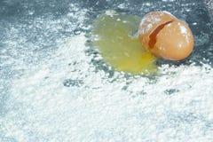 Ett brutet ägg på en yttersida som täckas i mjöl arkivbilder