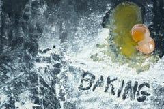 Ett brutet ägg på en yttersida som täckas i mjöl med ordet arkivbilder