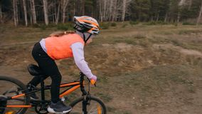 Ett caucasian spår för väg för barnrittcykel i smuts parkerar Orange cirkulering för flickaridningsvart i löparbana Ungen går att arkivbilder