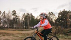 Ett caucasian spår för väg för barnrittcykel i smuts parkerar Orange cirkulering för flickaridningsvart i löparbana Ungen går att royaltyfri fotografi