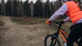 Ett caucasian spår för väg för barnrittcykel i smuts parkerar Orange cirkulering för flickaridningsvart i löparbana Ungen går att royaltyfri bild