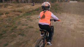 Ett caucasian spår för väg för barnrittcykel i smuts parkerar Orange cirkulering för flickaridningsvart i löparbana Ungen går att royaltyfria foton