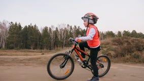 Ett caucasian spår för väg för barnrittcykel i smuts parkerar Orange cirkulering för flickaridningsvart i löparbana Ungen går att royaltyfria bilder