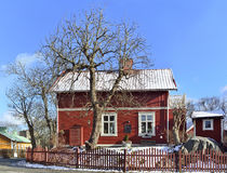 Ett charmigt rött hus med vitklippning om den tidiga vårdagen i Vaxholm Arkivbilder