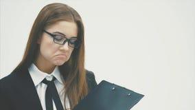 Ett charmigt ungt affärsflickaanseende på en vit bakgrund stock video