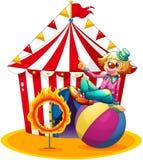 Ett clownsammanträde ovanför en boll bredvid en cirkel av brand framme av Royaltyfri Foto