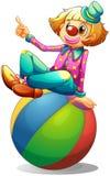 Ett clownsammanträde på en boll Royaltyfria Bilder