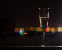 Ett crystal exponeringsglas med champagne med bubblor på natten på färgrik belysningbakgrund Royaltyfri Foto