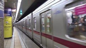 Ett drev som stoppar på gångtunnelstationen i Tokyo, Japan arkivfilmer