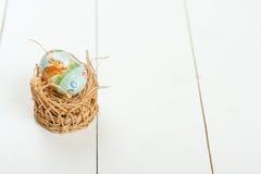 Ett easter ägg med en modell i ett rede över träbakgrund Ägg, knäpp blomma och randig torkduk Royaltyfria Bilder