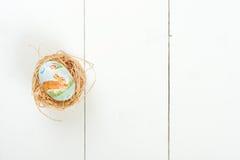 Ett easter ägg med en modell i ett rede över träbakgrund Ägg, knäpp blomma och randig torkduk Fotografering för Bildbyråer