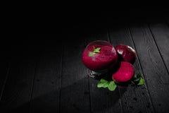 Ett efterrättexponeringsglas med vin-färgad tunn välling på en svart bakgrund Sund smoothie med rödbeta, mintkaramellen och socke arkivbild