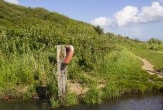 Ett eftersatt hjälpmedel för livbesparingflytförmåga på en liten spång på banan för Solent vägstrand på Southampton vatten royaltyfri foto