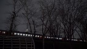 Ett elektriskt drev förbigår stationen på natten arkivfilmer