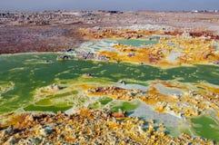 Ett enormt grönt fält med gula fläckar av svavel- volcanoes för lava bland den rosa jorden av öknen av Danakil, den avlägsna hand Royaltyfria Bilder