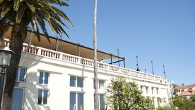 Ett enormt vitt mång--våning gods i palmträd Herceg Novi, måndag lager videofilmer
