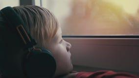 Ett ensamt barn i hörlurar som lyssnar till musik och ut ser fönstret Barnet är deprimerat stock video
