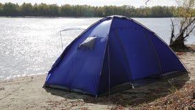 Ett ensamt blått tält som är uppblåst vid en stark vind på banken av en höstflod arkivfilmer