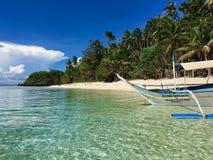 Ett ensamt fartyg på den sandiga stranden för paradis, med klart vatten, Phil arkivbild
