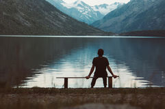 Ett ensamt mansammanträde på bänken framme av sjön royaltyfri foto