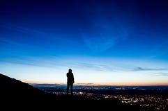 Ett ensamt med huva diagram på en kulle silhouetted precis för soluppgång som ut ser på stadsljus Royaltyfria Bilder