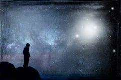Ett ensamt med huva diagram silhouetted och att stå på en kulle som ser en galax på natten med ufo som svävar i himlen Med en gru royaltyfri fotografi