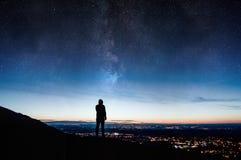 Ett ensamt silhouetted med huva diagram Stå på en kulle som ser ner på stadsljus på natten med en galax och stjärnor som stiger i arkivfoto