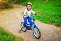 Ett entusiastiskt gladlynt barn på en cykel i gräsplan parkerar är lyckligt och skriker med spänning av gyckel Arkivbild