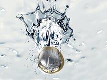 Ett euromynt faller in i vatten Arkivbilder