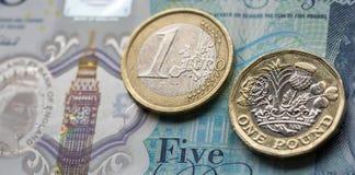 Ett euromynt och ett pundmynt på en brittisk fem pund anmärkning i ett horisontalformat Royaltyfri Fotografi