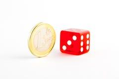 Ett euromynt och röd tärning en Royaltyfri Fotografi