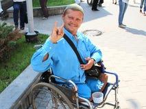 Ett exempel av optimism och själsstyrka från en rörelsehindrad person i en rullstol arkivbilder
