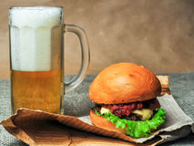 Ett exponeringsglas av öl och en ostburgare på ett hantverk skyler över brister Arkivfoto