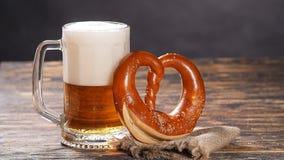 Ett exponeringsglas av öl och kringlan på en trätabell stock video
