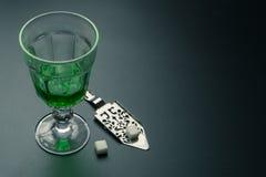 Ett exponeringsglas av absint och en rostfritt st?l placerad sked royaltyfri bild