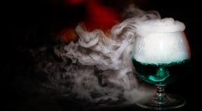 Ett exponeringsglas av alkohol med rök royaltyfri bild