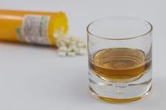 Ett exponeringsglas av alkohol och en flaska av preventivpillerar Royaltyfri Bild