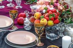 Ett exponeringsglas av champagne med frukt på brölloptabellen arkivfoton
