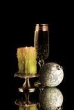 Ett exponeringsglas av Champagne med stearinljuset och jul klumpa ihop sig Royaltyfria Bilder