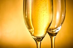 Ett exponeringsglas av champagne och en som är tomma med guld- bubblor och utrymme för text Arkivbilder