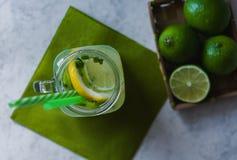 Ett exponeringsglas av citronjuice och stycken av limefrukt och citronen arkivfoto