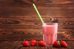 Ett exponeringsglas av den nya och söta smoothien på en brun trätabell Några jordgubbar är nära ett fullt exponeringsglas av drin Arkivfoton