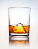 Ett exponeringsglas av drinken och ett stycke av is på en vit bakgrund Royaltyfria Bilder