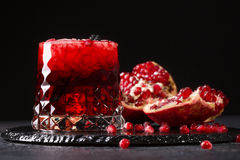 Ett exponeringsglas av en granatäppledrink med is och klippt granatrött på en svart bakgrund Nya och organiska sommarcoctailar royaltyfri bild