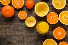 Ett exponeringsglas av fruktsaft och klippta apelsiner och mandariner på träbacen Royaltyfri Foto