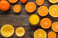 Ett exponeringsglas av fruktsaft och klippta apelsiner och mandariner på träbacen Royaltyfri Fotografi