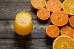 Ett exponeringsglas av fruktsaft och klippta apelsiner och mandariner på träbacen Arkivfoto