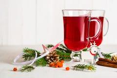 Ett exponeringsglas av glödhett funderat vin på en ljus bakgrund kortjul som greeting nytt år Arkivbild