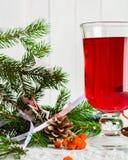 Ett exponeringsglas av glödhett funderat vin på en ljus bakgrund kortjul som greeting nytt år Arkivfoto