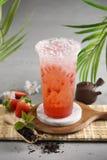 Ett exponeringsglas av gr?nt te D?r n?gon skivad limefrukt i krukan f?r platta och lite f?r gr?splante royaltyfria bilder